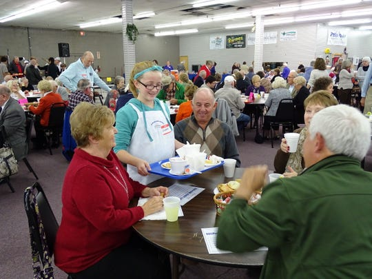 Elizabeth Molnar, 11, clears a table for attendees of the SOUPer Bowl Sunday at the Muskingum County Center for Seniors. The annual event raised about $15,000 in 2013 and has donated close to $200,000 in 18 years to five local charities for feeding the hungry. About 120 volunteers usually help serving around 1,000 guests.