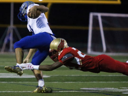 The Eagles of Edison High School take on the Bombers from Sayreville War Memorial High School in a varsity football at Edison on Friday September 16, 2016Edison's # 22 (right) Noah Stansbury trips up Sayreville's # 15 Matt Lubeski.