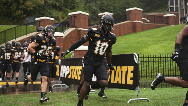 Appalachian State football players make their entrance to the field prior to an NCAA college football game against UNC-Charlotte on Saturday, Sept. 12, 2020, in Boone, N.C.