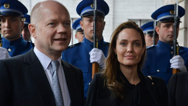 UNHCR goodwill ambassador Angelina Jolie and British Foreign Secretary William Hague pose for photographers upon their arrival for a meeting with the Bosnian Presidency in Sarajevo, Bosnia, on Friday March 28, 2014. British Foreign Secretary William Hague and Hollywood star Angelina Jolie addressed a conference organized in Sarajevo by Bosnia's Defense Ministry on sexual violence in conflict.