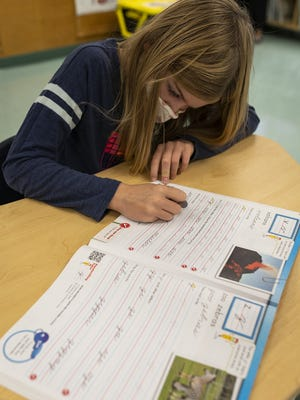Fourth-grader Graham Binnick practices in a cursive workbook at Hildreth Elementary School in Harvard.