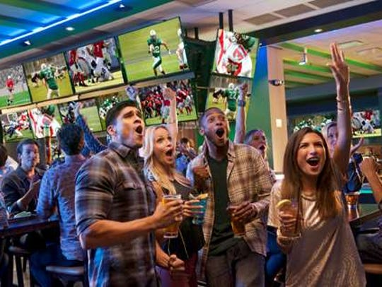 A group cheers in the sports bar area of a Dave & Buster's.