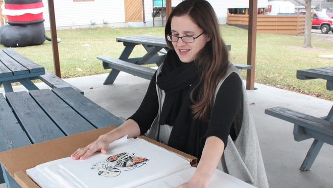 Stevens Point native Anne Sell, a graphic designer, looks through her art portfolio Thursday. Sell's design for a beverage can is in the running to be featured on Mike's Harder Passion Fruit.