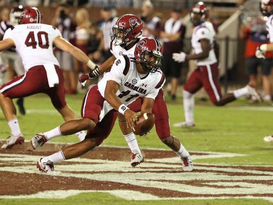FILE - In this Sept. 10, 2016, file photo, South Carolina quarterback Brandon McIlwain (11) picks up the ball after it was snapped over his head during the second half of an NCAA college football game against Mississippi State in Starkville, Miss. Mississippi State won 27-14. Senior Perry Orth has started the first two games. But freshman Brandon McIlwain may get the chance against fired-up East Carolina on Saturday. (AP Photo/Jim Lytle, File)