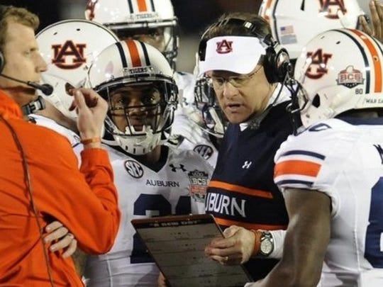 Auburn coach Gus Malzahn (center) goes over a play during a timeout in 2014.