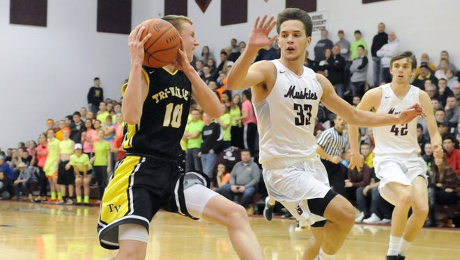 John Glenn's Drew Rackley defends Tri-Valley's Marcus Dempsey during the Muskies' 75-54 victory over the Scotties on Wednesday in New Concord.