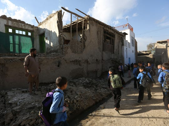 Afghan school boys walk to look a damaged house following a powerful earthquake that could be felt across South Asia, in Kabul, Afghanistan, Monday, Oct. 26, 2015. In Afghanistan's Takhar province, west of Badakhshan, at least 12 students at a girls' school were killed in a stampede as they tried to get out of the shaking buildings, a local official says. Sonatullah Taimor, the spokesman for the Takhar provincial governor, says another 30 girls have been taken to the hospital in the provincial capital of Taluqan. (AP Photo/Rahmat Gul)