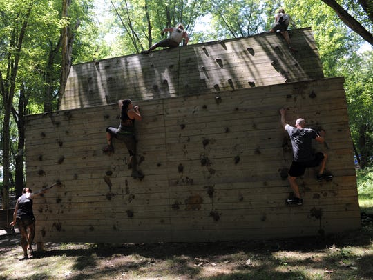 Challengers work their way up a climbing wall during a previous Indian Mud Run at Lake Park in this Tribune file photo. The seventh annual event expects to draw more than 600 people from across the country and Canada.