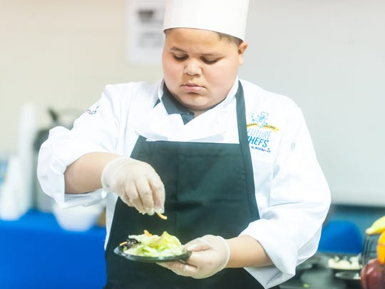 Tayten Frederiksen prepares his 'Refreshingly Light Oriental Salad' during Vineland's Junior Chef competition on Wednesday, March 22 at Wallace Intermediate School.