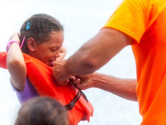 Mike Martin helps Amelia Stinson into a life vest for
