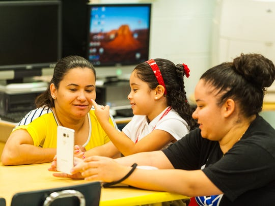 Winslow kindergartner Iliana Valencia FaceTimes with the assistance of Barbarita Clarke and Ashley Almeda on the first day of school at Winslow Elementary on Wednesday, September 6.