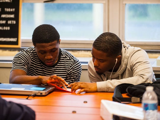 Millville seniors Damion Bowser and Lonnie Broome Jr look over paperwork during homeroom on the first day back at Millville Senior High on Wednesday, September 6.