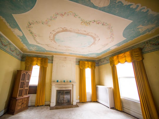 A front room with a mural on the ceiling inside the