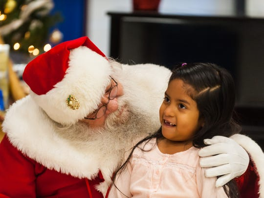 Victoria Cajamarca meets with Santa at Somerdale Park School. The school organized a gift drive and visit with Santa for immigrant and refugee families.