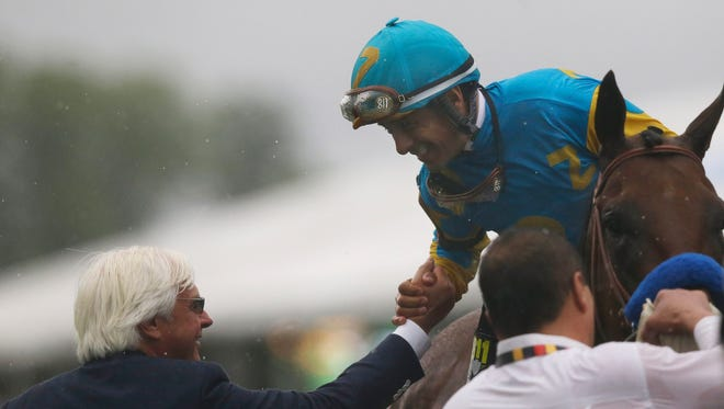 Jockey Victor Espinoza aboard American Pharoah and Bob Baffert, left, celebrate after winning the 140th Preakness Stakes horse race at Pimlico Race Course.