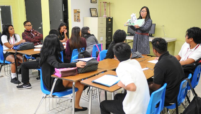 "Teacher Acie Jo Cruz, standing, demonstrates an example of an ""interactive student notebook"" that she has planned as an assignment for the seniors attending her English class at Simon Sanchez High School in Yigo on Monday, Aug. 17, 2015."