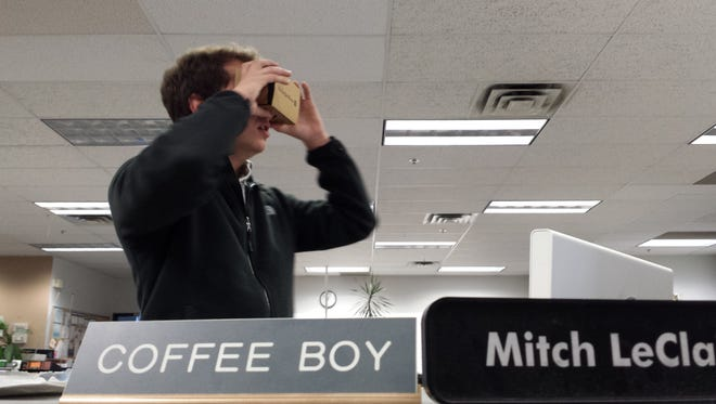 Ben Rodgers, breaking news reporter, tries the Google Cardboard viewer in the St. Cloud Times newsroom.
