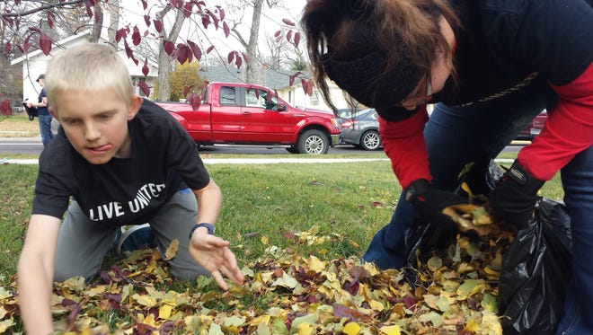 With school out for the day, Luke Swensson joins other volunteers raking leaves during the United Way's annual Day of Caring.