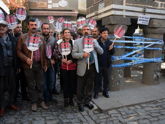 Tahir Elci, the head of Diyarbakir Bar Association, front right, speaks to the media shortly before being shot dead in Diyarbakir, Turkey, Saturday, Nov. 28, 2015.