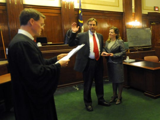 Buncombe County Assistant District Attorney Rodney Hasty with wife Candace listen as Buncombe County Judge Alan Thornburg reads the oath of office during a special ceremony held at the courthouse Thursday Jan. 1, 2015.