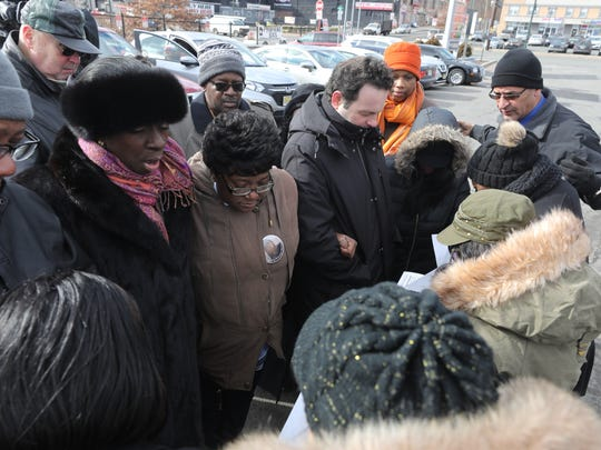Willie Coley, father of missing woman Shanaya Coley, with Dr. Lilisa Mimms, who leads the group in prayer. The missing woman's mother, Rachel Coley, Paterson Councilmen Andre Sayegh and Luis Velez follow in prayer.
