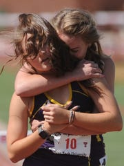 Wylie's Kylie Thornton, rear, hugs teammate Madison Latham after Latham finished second in the girls 300 hurdles at the Region I-4A track and field meet.