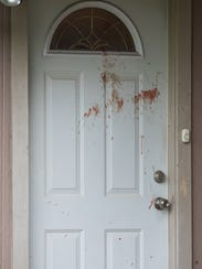 Blood on the door of the neighboring home where law