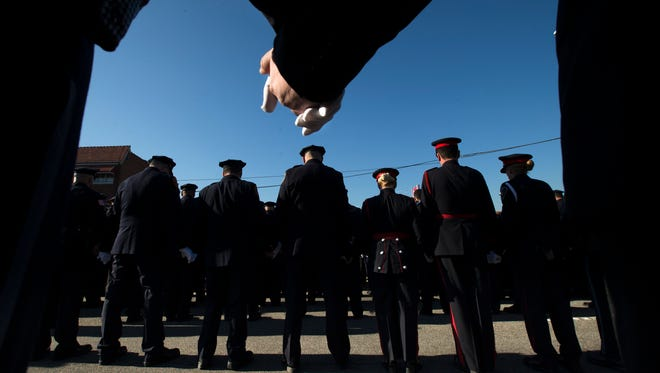 Police officers hold hands in prayer during the funeral service of New York City police officer Rafael Ramos in the Glendale section of Queens on Saturday in New York. Ramos and his partner, officer Wenjian Liu, were killed Dec. 20 as they sat in their patrol car on a Brooklyn street. The shooter, Ismaaiyl Brinsley, later killed himself.