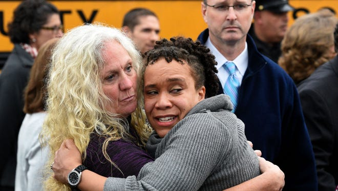 Clovis Stair, left, supervisor of Knox County School psychology, consoles Sunnyview Primary School Principal Sydney Upton near the scene where two school buses serving Chilhowee Intermediate School and Sunnyview Primary School crashed in Knoxville, Tenn., Tuesday, Dec. 2, 2014. Standing behind them is Knox County Schools Superintendent Jim McIntyre.  At least three people died in the accident.  Two buses carrying children home from school collided on a Tennessee highway killing two students and an adult and injuring another 23 people.  Knoxville Police Chief David Rausch said the children who died were between the ages of kindergarten and third grade. The adult who died was an aide.   (AP Photo/Knoxville News Sentinel, Michael Patrick)