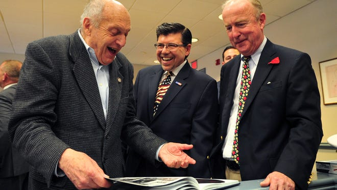 World War IIArmy veteran Harry Ettlinger, left, of Rockaway Township looks through a book of cultural artifacts saved by the Monuments Men with Assemblyman Anthony Bucco and Rep. Rodney Frelinghuysen, right, in 2014