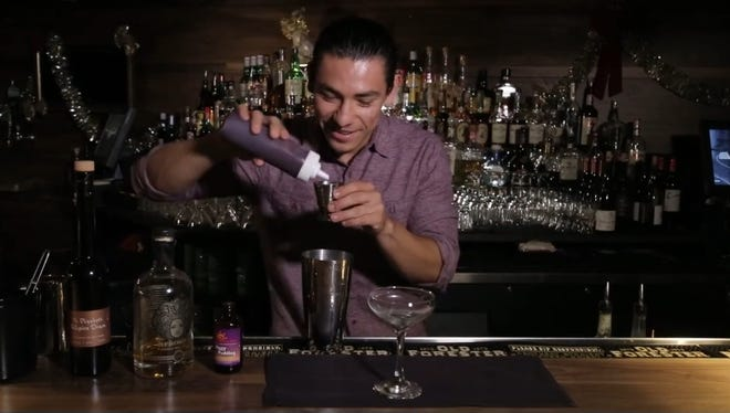 Jorge Rivera of the Womack in Phoenix smiles as he shows how to make Where's My Figgy Pudding, a festive holiday cocktail with rum.