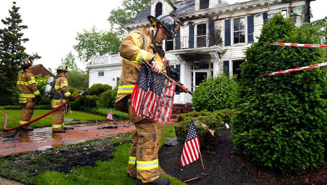 Toms River Fire Department District 1 firefighter Dave Klemick pics up soiled flags from the front of 236 Washington Street in Toms River that was destroyed by an early morning fire Tuesday, May 31, 2016.  A sign outside listed the occupants as Childers Sotheby's International Realty, Oliver & Co. Insurance Adjusters and Hometown Heroes.