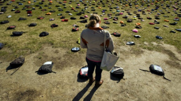 Ashley Koetsier, 21, of Woodstock, Vt., reads about a college student who died by suicide from a small laminated plaque attached to a backpack on the green outside Davis Center at the University of Vermont in Burlington, Vt.  Active Minds placed 1,100 backpacks representing victims, dozens with personal stories of student suicide. (AP Photo/The Burlington Free Press,  Ryan Mercer)