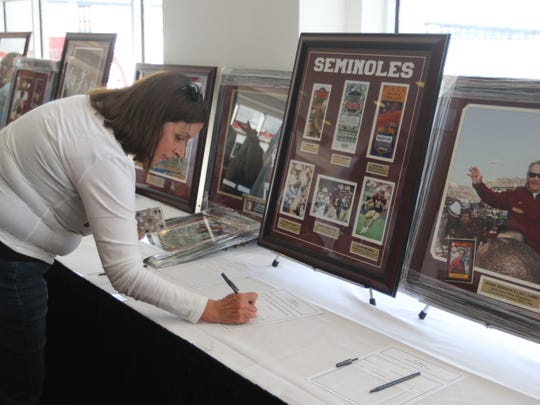 Jane Hatfield places a bid during a Seminole Boosters
