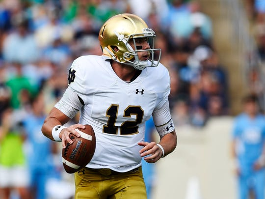 Notre Dame Fighting Irish quarterback Ian Book (12) looks to pass in the first quarter at Kenan Memorial Stadium.