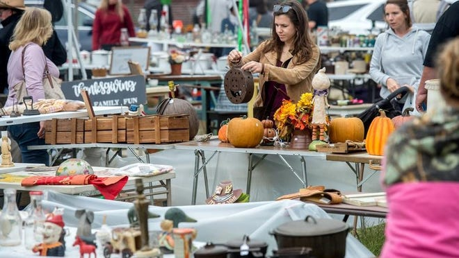 Customers work their way through tables teeming with items Saturday, Oct. 5, 2019, on the Spoon River Drive in London Mills.