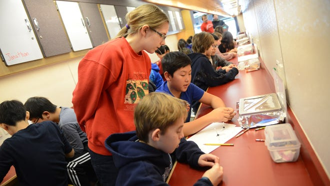 Rachel Gula, a Rutgers graduate oceanography student and Science Bus fellow helps Norwood Public School students Andrew Pinkus and Eric Cha build oil molecules on Jan. 10, 2017. The bus visited Norwood to teach sixth-grade students about oil and how to drill for it.
