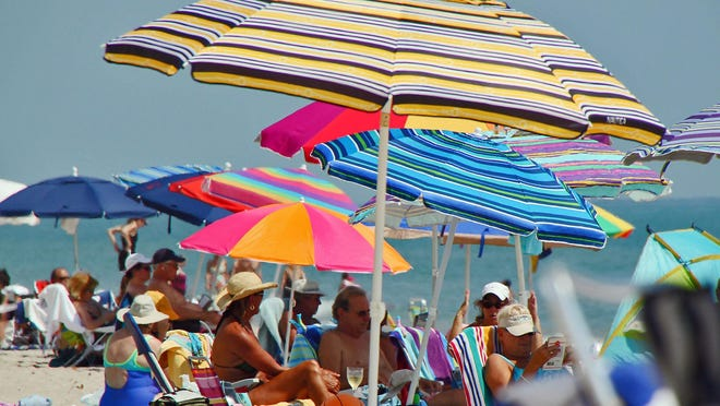 People huddled under their brightly colored umbrellas at  Lake Worth Beach Sunday to escape the record-breaking, 90-degree heat.
