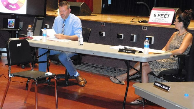 Frankfort-Schuyler Deputy Superintendent Joseph Palmer, left, is administered the Oath of Faithful Performance during Tuesday's school board meeting, as Board President Lisa Morgan looks on.