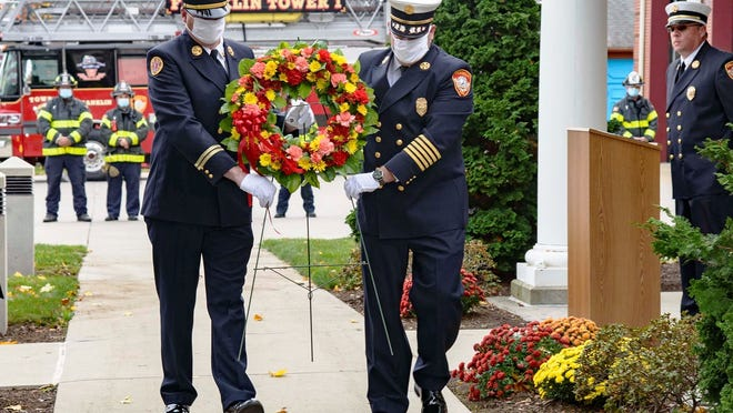 Franklin Fire Department Battalion Chief Chuck Allen, left, president of Local#2637, and Fire Chief James McLaughlin carry a wreath to be placed in front of the Franklin Fire Department headquarters during a memorial service for the department's departed members.