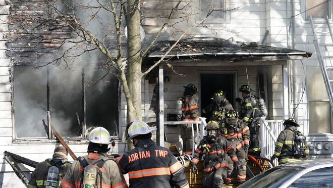 Firefighters from multiple responding departments battle recurring flames and hot spots after a large fire Monday at a multifamily rental house on Butler Street in Adrian.