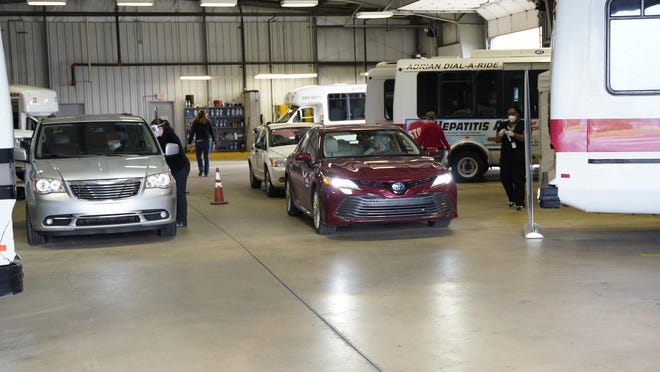 Drivers stop in the city of Adrian/Lenawee County transportation garage in Adrian to have COVID-19 tests administered Saturday.
