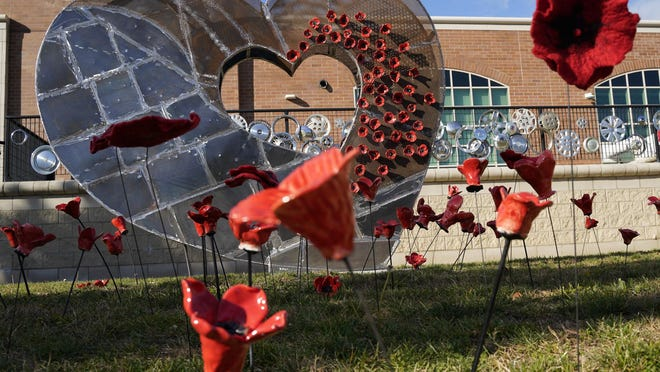 """Ceramic and felted wool poppies created by Tecumseh High School students as part of the Poppy Project in honor of Veterans Day, adorn the newly installed """"Open Heart"""" sculpture at the school's sculpture garden."""