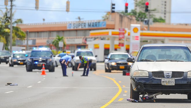 A child's bicycle can be seen wedged underneath a Nissan sedan as officers with the Guam Police Department conduct an investigation of an auto-bike collision on Route 10, near the Mobil Gas Station in Mangilao, on Thursday, June 23. A five-year-old girl with serious injuries was transported to Naval Hospital Guam, said Guam Fire Department spokesman firefighter Kevin Reilly.