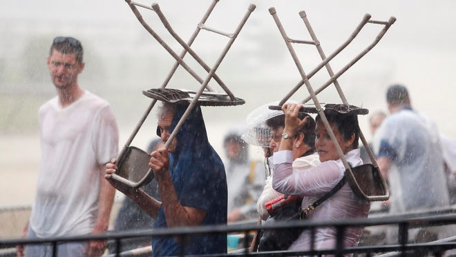 May 16, 2015; Baltimore, MD, USA; Fans try to take cover under chairs during a thunder storm before the 140th Preakness Stakes at Pimlico Race Course. Mandatory Credit: Peter Casey-USA TODAY Sports