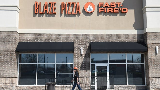 An employee walks past a  Blaze Fast Fire'd Pizza storefront at Turkey Creek in Knoxville.