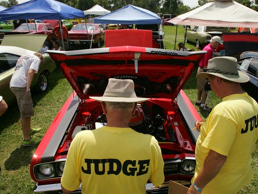 Ron Gillespie, left, and Mike Wilkins, of Nashville, Tennessee, judge a 1969 Roadrunner two-door hardtop with a 426 Hemi owned by Jim Bickel, Friday, at National Trail Raceway. The 426 is celebrating its 50th anniversary.