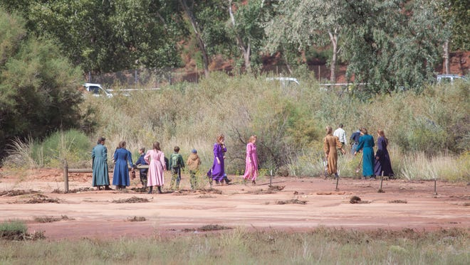 Residents of Short Creek search for missing people Tuesday, Sept. 15, 2015 after a flash flood swept families and vehicles downstream.