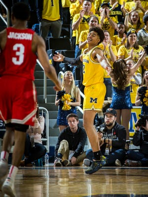 Michigan guard Jordan Poole, right, celebrates making a 3-point basket in the second half of U-M's 74-62 win on Sunday, Feb. 18, 2018, at Crisler Center.