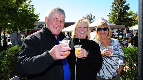 Farmington residents Neil and Alison Baker, along with Carol Charboneau of Northville, enjoy a cup of smoked wheat Polish beer (Piwo) at the Polish Festival held in conjunction with the Farmington Farmers Market.